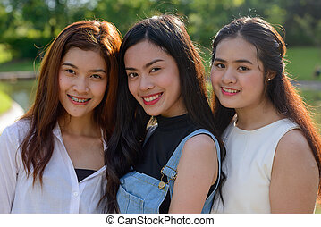 Three young Asian women as friends together at the park
