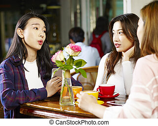 three young asian women chatting talking in coffee shop