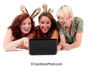 Three young attractive women lying on the floor cross-legged...