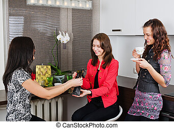 Three young beautiful women drink tea at a birthday