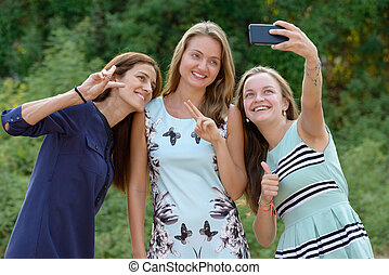 Three young beautiful women together at the park outdoors