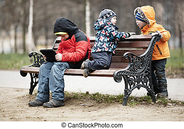 Three young boys playing on a park bench in winter wrapped up warmly against the cold weather with one youngster reading a tablet as the two younger children romp around