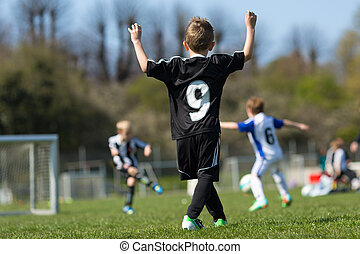 Three young boys playing soccer