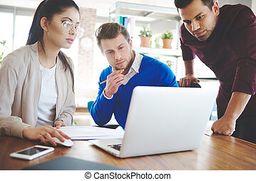Three young business people over work