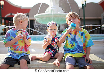 Three Young Children Eating Ice Cream by Fountain on Summer Day