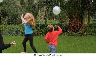 Three young children having fun hitting balloons in a park -...