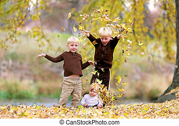 Three Young Children playing in Fallen Leaves