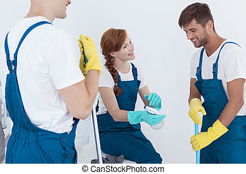 Three young cleaners - Three happy young cleaners talking...