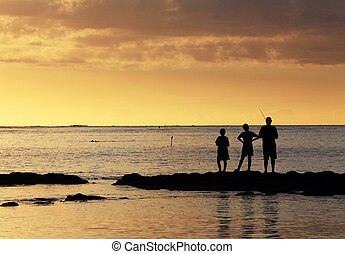 Three young fishermen are on the beach at sunset.