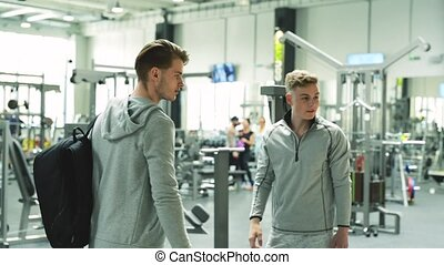 Three young fit men in gym greeting each other. - Three...