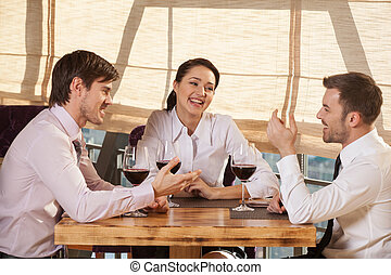 Three young friends having wine together in cafe. two man and woman seated around small table chatting and smiling