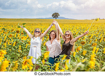 Three young friends in a sunflower field
