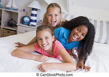 Three Young Friends Lying On Top Of Each Other
