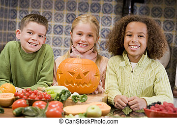 Three young friends on Halloween with jack o lantern and food smiling