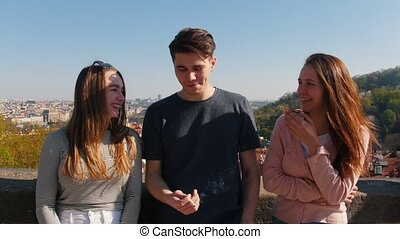 Three young friends standing on a observation deck and...