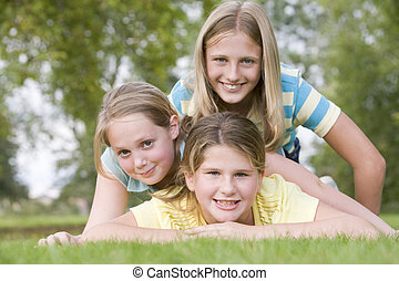 Three young girl friends piled on each other outdoors smiling