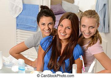 Three young girl friends posing in bathroom