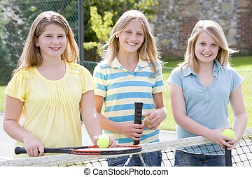 Three young girl friends with rackets on tennis court smiling