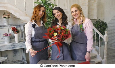 Three young handsome chef florists pose smiling in camera with ready fruit bouquet