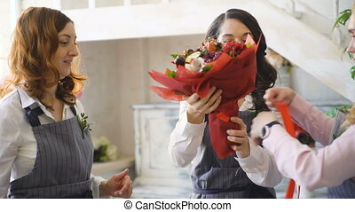 Three young handsome chef florists work at flowers fruit...