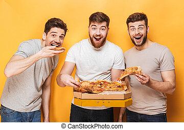 Three young happy men eating big pizza