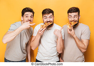 Three young happy men eating pizza