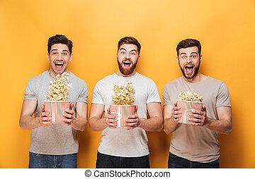 Three young happy men eating popcorn