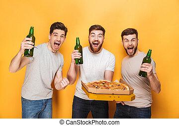 Three young happy men holding a big pizza