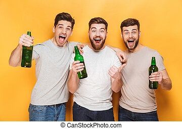 Three young happy men holding beer and celebrating