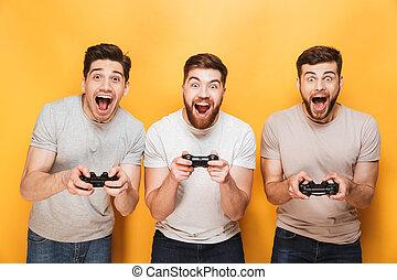 Three young happy men holding joysticks