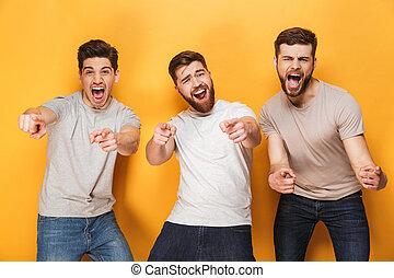 Three young happy men pointing at camera