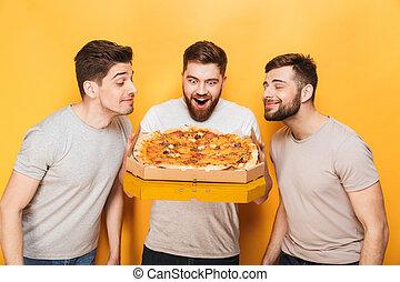 Three young happy men smelling a big pizza