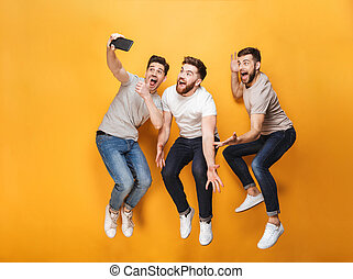 Three young happy men taking a selfie together