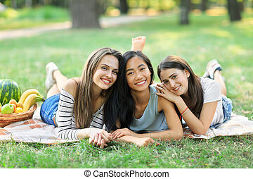 Three young happy multiracial women lying on grass in park
