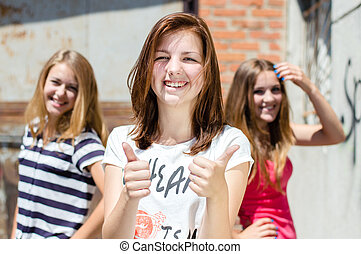 Three young happy teenage girls showing thumb up