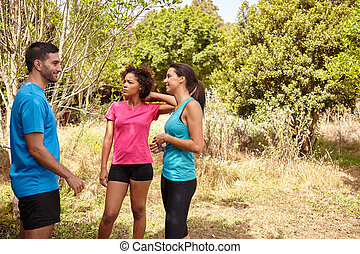 Three young joggers smiling on a break - Three happy young...