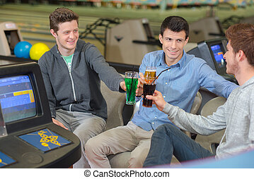 Three young men at bowling alley, toasting with their drinks