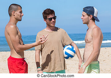 three young men at the beach holding a ball