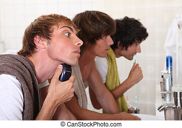 Three young men in the bathroom getting ready to go out