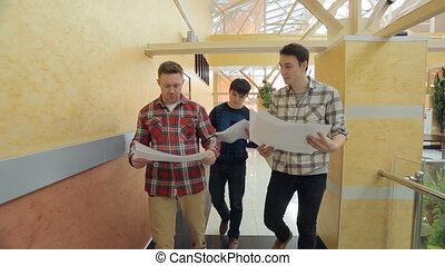 Three young men look at blueprint, discuss, move.