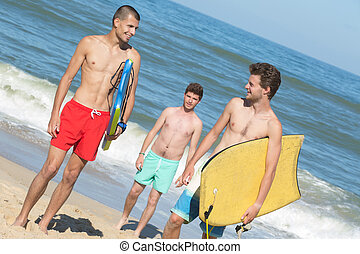 three young men on beach holding bodyboards
