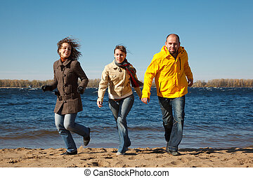 Three young men running down beach at camera holding hands with sunny autumn day.