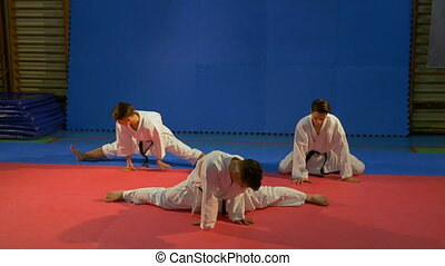 Three young men wearing karate kimonos doing stretching...