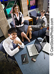 Three young office workers working in meeting room