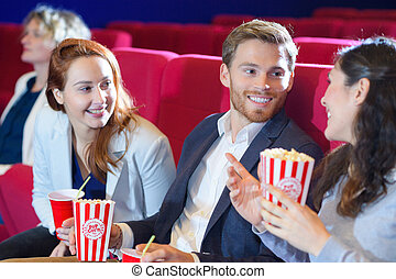 three young people chatting in cinema seats