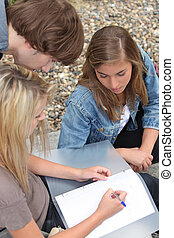 Three young people, one of them writing in a binder on her lap.
