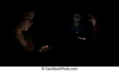 Three young people spending their time in the same room but using social media to socialize