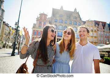 Three young people stand on the square of the ancient city.