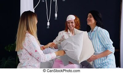 Three young sexy women pillow fighting at a slumber party in...