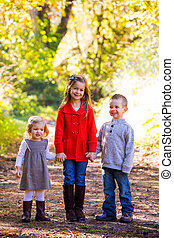 Three Young Siblings - Three children stand together ...